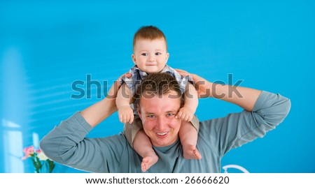 Young father lifting happy baby boy ( 1 year old ) at home, smiling.