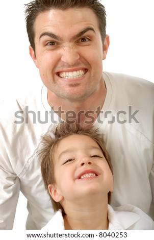 Young father making funny scary faces with his little son