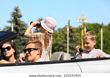 Young father, mother and two children ride in convertible car and play at summer day