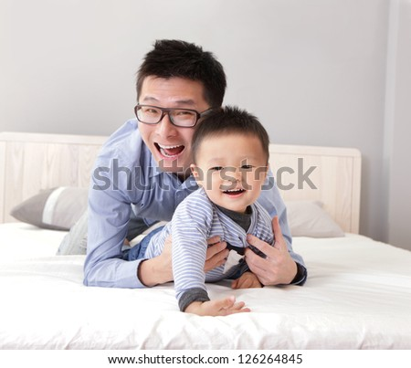 young father play with his son boy on the bed at home, asian lifestyle