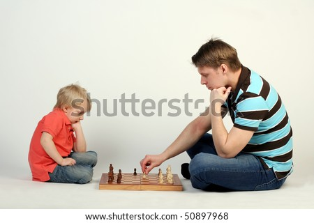 Young father playing chess with his little cute son