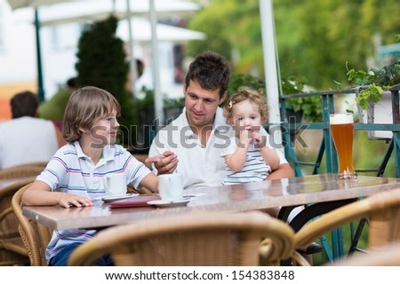 Young father relaxing in an outside cafe with his children, a school boy and cute curly baby girl having a drink together on a nice warm summer day