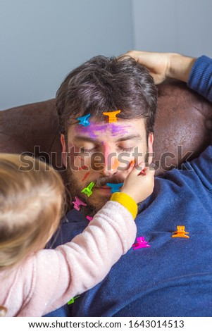 Young father suffering the mischief of his little daughter. Little girl paints with brush and watercolors her father's face while he sleeps on the couch Stock photo ©