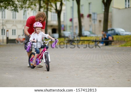 Young father teaching his daughter to ride a bicycle