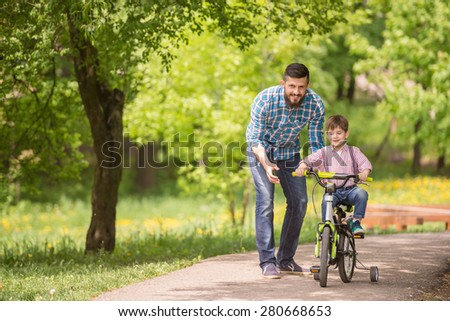 Young father teaching son to ride bicycle in summer park.