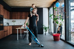 Young father vacuum cleaning apartment floor with his infant baby riding on his neck. Entertaining baby, while doing necessary chores.
