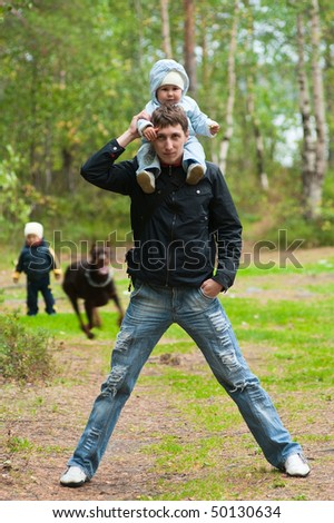 Young father walking with two children and dog. Little girl on shoulders and son and dog on background. Summer time