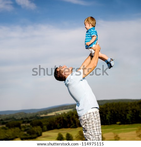 young father with a little son on the meadow