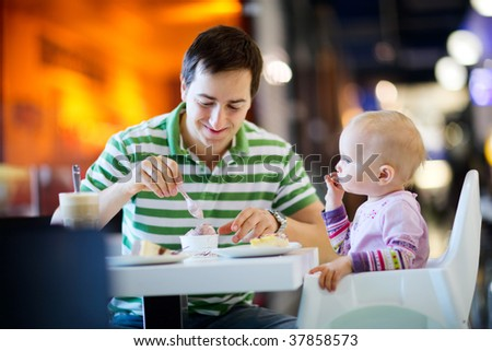 Young father with baby daughter enjoying meal sitting at cafe - stock photo