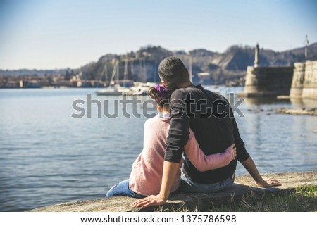 Young father with daughter sitting on the lake shore watching the boats at sea Daddy looks at the horizon near little gir  Relaxing peaceful weekend Concept of family and affection, strong bond