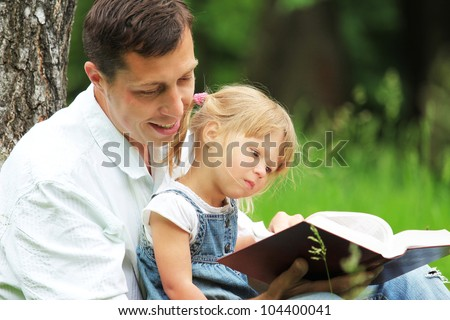 Young father with his daughter reads the Bible - stock photo