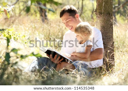 young father with his daughter reads the Bible