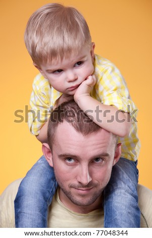 Young father with little son on his shoulders