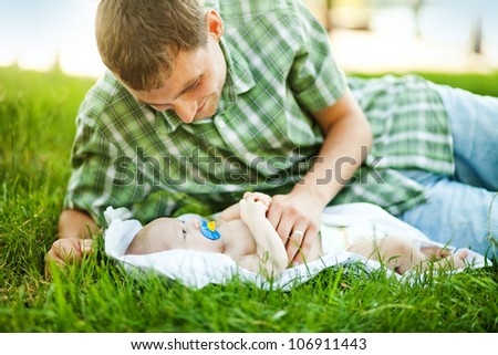 Young father with son outdoors in park, soft focus (focus on eyes of baby)
