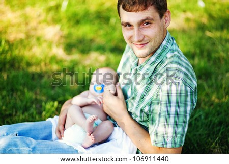 Young father with son outdoors in park, soft focus (focus on eyes of father)