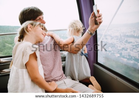 Young father with two girls taking picture sitting in a cabin of the giant wheel