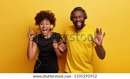 Young fellows have boosting mood, sing and dance together, find cool tracks for disco party, wears black and yellow clothes, have dark skin, shake hands, feel happy and playful, move with joy
