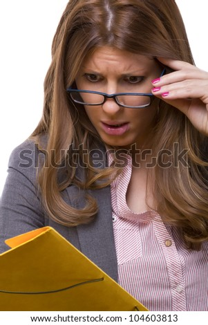 Young female accountant holding the glasses, being worried about the data on her work sheets, bad news at work
