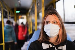 Young female adult commutes in a protective face mask. Coronavirus, COVID-19 spread prevention concept, responsible social behaviour of a citizen