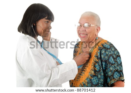 Young female African American nurse or doctor checking elderly African American woman's heart, isolated on white.