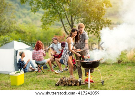 Young female and male couple baking barbecue in nature