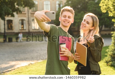 Young female and male friends in the park posing for selfie on smartphone camera, millenial students taking photo on mobile phone holding notebooks while having a coffee break in college campus. #1460359982