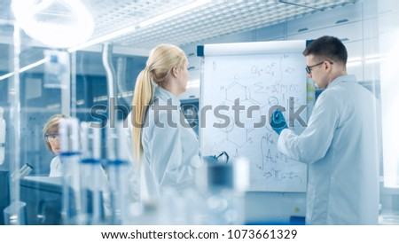Young Female and Male Scientists Write Formulas on a Whiteboard. They're Solving Scientific Problems in Bright Modern High Tech Laboratory.