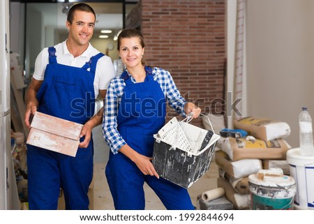 Young female and male workers holding bricks during decorating work in room