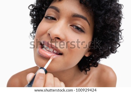 Young female applying lipstick with a lip brush in a concentrated way