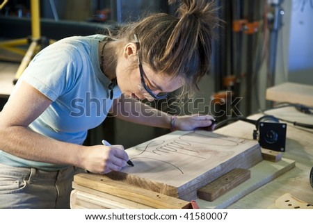 Young female apprentice using a router in a woodshop. - stock photo