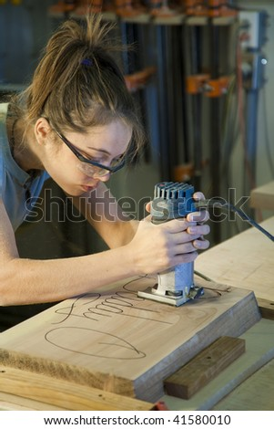 Young female apprentice using a router in a woodshop.