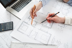 Young female architect and designer working on blueprint project of new apartments. Photo concept of work on technical drawings