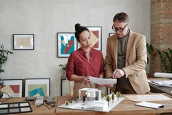 Young female architect and her mature male colleague holding paper over model of new house and yard while discussing details of sketch