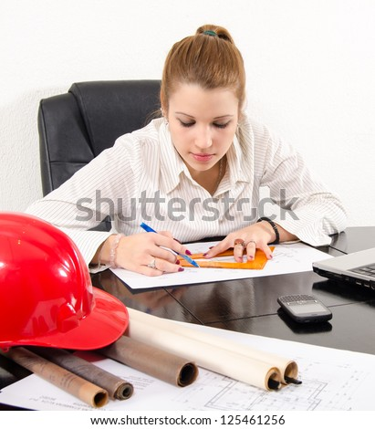 Young female architect working on the project in her office.