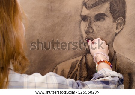 Young female artist drawing man portrait in her art studio.