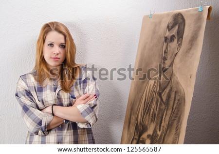 Young female artist posing beside her artwork.