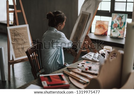 Young female artist sitting at the table with creative tools and turning to the drawing on the easel