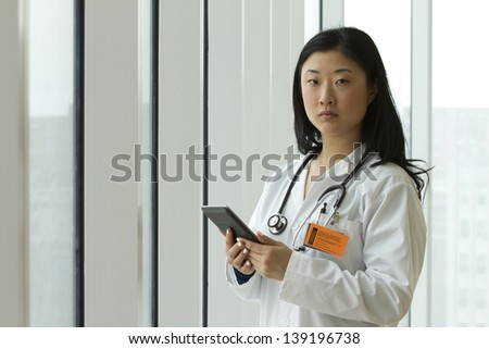 Young female Asian doctor holding a tablet