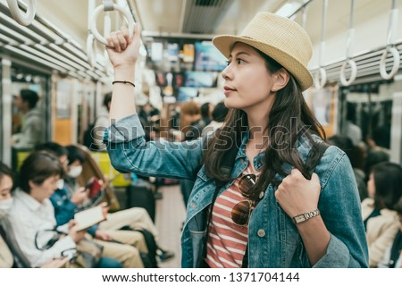 young female asian traveler hand holding handle standing on subway train. elegant lady with straw hat commute by public transport in japan osaka. people in metro doing self thing quiet sitting seat
