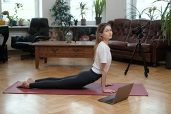 Young female athlete dressed in sportswear shows yoga poses on mat using laptop and photocamera in room.
