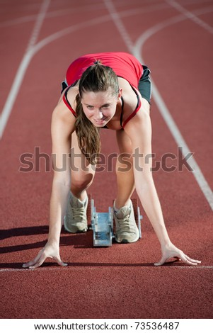 Young female athlete on a running track, ready to go from starting blocks