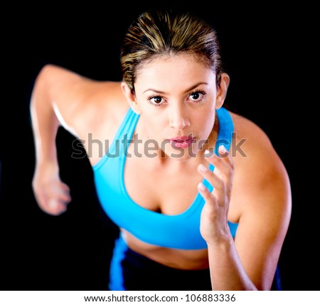 Young female athlete running - isolated over a black background