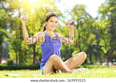 Young female athlete seated on a green grass exercising with dumbbells in a park