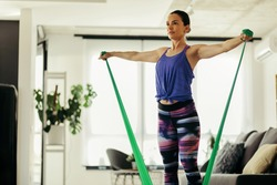 Young female athlete using resistance band while working out in the living room.