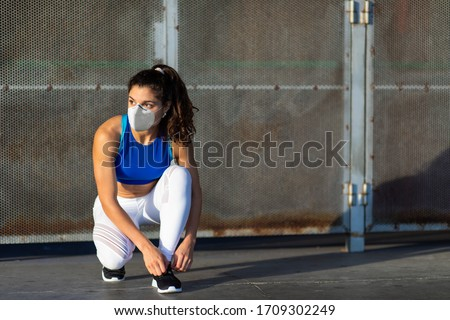 Young female athlete with face mask for protecting against Covid-19 contagion getting ready for urban running and fitness workout. Motivated woman training outside under coronavirus health crisis.