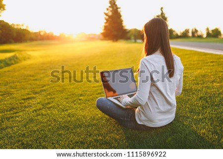 Young female back view. Woman working on laptop pc computer with blank black empty screen to copy space in city park on green grass sunshine lawn outdoors. Mobile Office. Freelance business concept
