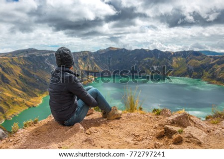 Young female backpacker/tourist contemplating the active Quilotoa crater lake with its turquoise waters along the Quilotoa Loop trek which is part of the Andes mountain range, Ecuador, South America.