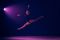 Young female ballet dancer dancing on neon lights studio background. Ballerina project with caucasian model. The ballet, dance, art, contemporary, choreography concept