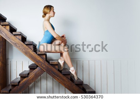Young female ballet dancer in the blue suit sitting on stairs #530364370