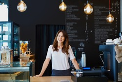 Young female barista standing behind the bar in cafe smiling